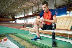 Deportista perjudicado que se sienta en banco después de entrenar imagen de archivo