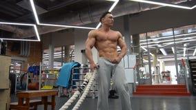 Deportista pposing con el entrenamiento pesado de la cuerda en el gimnasio almacen de metraje de vídeo