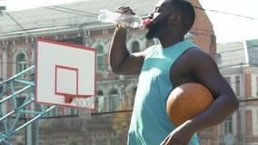 Deportista que bebe de la botella, restableciendo el equilibrio de agua después del entrenamiento activo metrajes