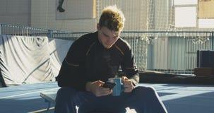 Deportista que come y que usa el teléfono metrajes