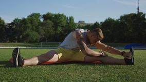 Deportista que dobla en la estera en campo verde almacen de metraje de vídeo