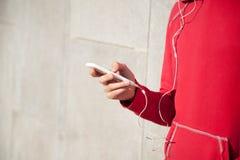 Deportista que escucha la música usando smartphone Fotografía de archivo libre de regalías