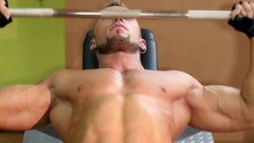 Deportista que hace ejercicios con la barra en el gimnasio almacen de metraje de vídeo