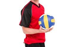 Deportista que lleva a cabo un voleibol Foto de archivo libre de regalías