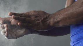 Deportista que pone el polvo de talco en las manos, atleta que se prepara antes de competencia almacen de video