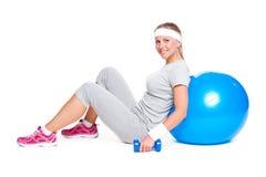 Deportista que se sienta con la bola y pesas de gimnasia Imágenes de archivo libres de regalías