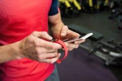 Deportista que usa el dispositivo de la aptitud en gimnasio imagen de archivo