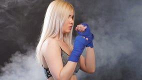 Deportista rubia atractiva en vendajes kickboxing en postura defensiva almacen de metraje de vídeo