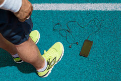 Deportista y smartphone con auriculares de botón en pista corriente azul Fotografía de archivo libre de regalías