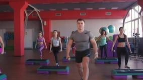 Deportistas jovenes atractivos que ejercitan con pesas de gimnasia almacen de video