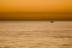 Deportistas que pescan en la puesta del sol Fotos de archivo
