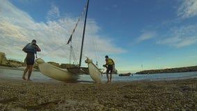Deportistas que toman el equipo del catamarán del windsurf en la orilla, resto activo metrajes