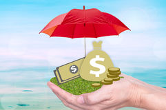 Deposit protection and protect currency. Deposit protection, protect investment or banking concept. money bag, banknote on hand with protected by umbrella Royalty Free Stock Photos