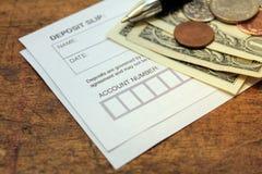 Deposit slip. Paper deposit slip, spare change and pen over wood background royalty free stock image