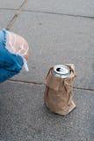 Deposite com cerveja em um pacote de papel no asfalto Imagens de Stock