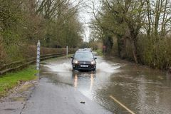 deposite los pasos holidaycar a través del camino inundado con el indicador de la advertencia y de medición Imagen de archivo