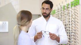 Deposito ottico Occhiali di Helping Woman Choosing dell'oculista stock footage