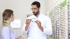 Deposito ottico Occhiali di Helping Woman Choosing dell'oculista video d archivio