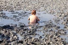 Deposits of natural healing clay. The child gladly accepts mud b. Deposits of natural grey healing clay. The child gladly accepts mud baths stock photos