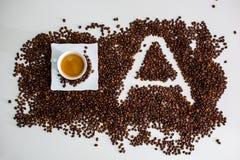Depozyty są lokalizować kawowej fasoli filiżanki kawą warzącym i wizerunkiem list A fotografia royalty free