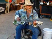 Deppighetkonstnär som spelar en akustisk gitarr på marknaden för Dane County Farmer ` s i Madison, WI arkivfoton