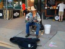 Deppighetkonstnär som spelar en akustisk gitarr på marknaden för Dane County Farmer ` s i Madison, WI Royaltyfri Fotografi