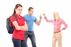 Deppressed teenager looking, parents arguing in the background. Deppressed teenager looking at camera with mother and father arguing in the background isolated Stock Photo