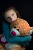 Depresión adolescente, muchacha que abraza un oso de peluche en la oscuridad Imagen de archivo libre de regalías