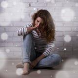 Depresión del invierno - mujer infeliz que se sienta en el piso Imagen de archivo libre de regalías