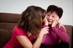 Depresión - la hija lamenta a la madre mayor imagenes de archivo