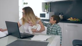 Depresión, mamá ocupada con el niño en sus manos que trabajan detrás del ordenador portátil en fondo del hijo de salto que interf almacen de video
