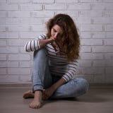 Depresión - mujer infeliz que se sienta en el piso Imagenes de archivo