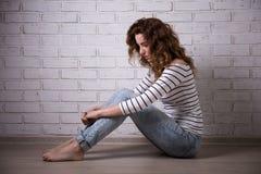 Depresión - mujer triste sola que se sienta en el piso sobre wa del ladrillo Imagen de archivo