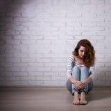 Depresión y soledad - mujer infeliz que se sienta en el piso o Imagen de archivo