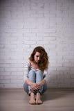 Depresión y soledad - mujer joven triste que se sienta en el piso Fotografía de archivo