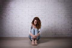 Depresión y soledad - mujer triste que se sienta en el piso encima Imagen de archivo