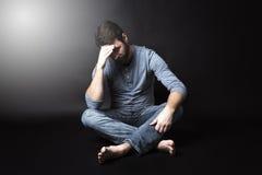Depresja kluczowy portret mężczyzna obsiadanie w zmroku i Obrazy Royalty Free