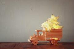 Depresja kluczowy wizerunek retro drewniany zabawkarski samochód z girland złotymi gwiazdami nad drewnianym stołem nostalgia i pr Obrazy Royalty Free