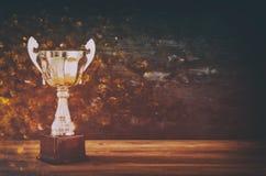 Depresja kluczowy wizerunek trofeum nad drewnianym stołu i zmroku tłem zdjęcia stock