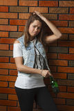 Depress drinker. Young twenty year old woman with depress expression and a bottle of beer Stock Photo