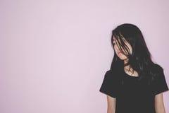 Depress and hopeless girl standing abuse concept. Depress and hopeless girl standing on pink background Stock Image