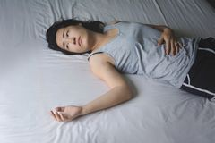 Depress and hopeless woman laying on bed. With absent minded Stock Photos