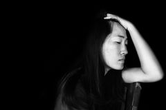 Depress and hopeless woman sitting on chair. On black in white tone Royalty Free Stock Photo