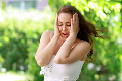 Depress woman outdoor. On green park in sunny day Stock Image