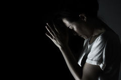 Depress woman praying in the dark  praying in secret room conce Stock Images