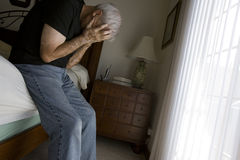 Depressed. Senior man in bedroom setting with natural light Royalty Free Stock Photography