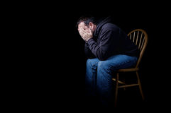 Depressed. A depressed man sitting in a chair with his hands over his face, shot on black Stock Photo