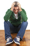 Depressed. Young depressed male sitting holding his head with both hands stock images