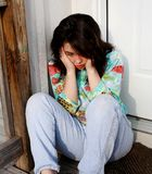Depressed. Young upset teen girl sitting on porch Stock Photo