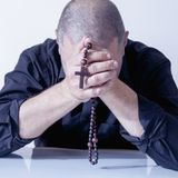 Depressed adult man praying with rosary beads as symbol of hope, faith and spirituality.  royalty free stock photo